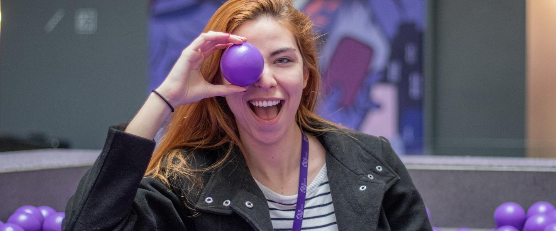 Una joven mujer sonríe y juego con una bola morada de plástico, que posa sobre su ojo derecho.