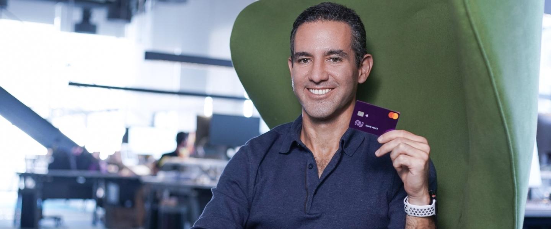 David Vélez, fundador y CEO de Nu, sonríe en las oficinas con una tarjeta de c rédito Nu morada en la mano.