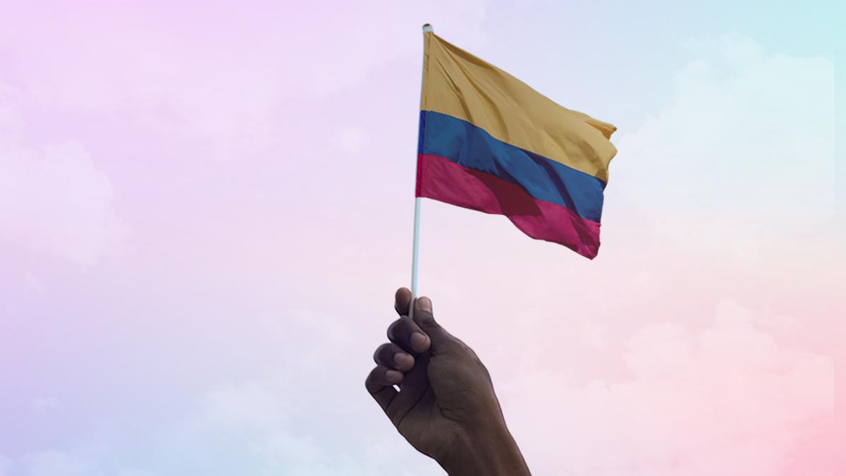 Una mano sostiene un banderín de Colombia