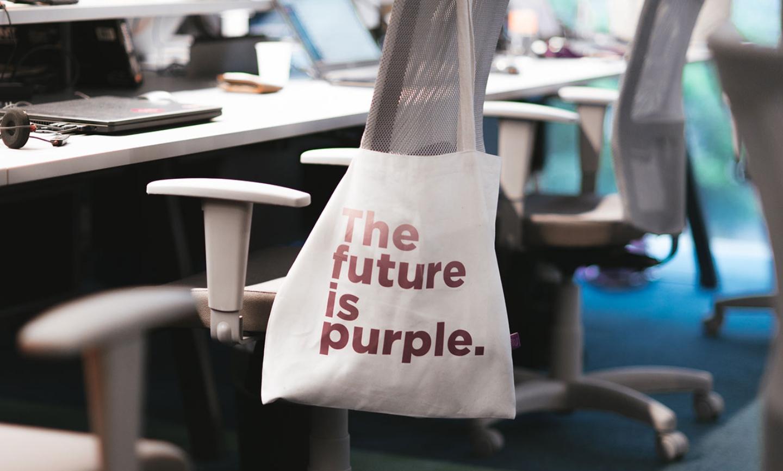 Una bolsa blanca con una inscripción en color morado que dice: