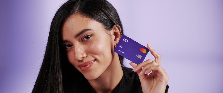 Una mujer joven colombiana, morocha, sonríe mientras sostiene la tarjeta de crédito Nu pegada a su rostro: lis lista de espera de Nu valió esta alegría