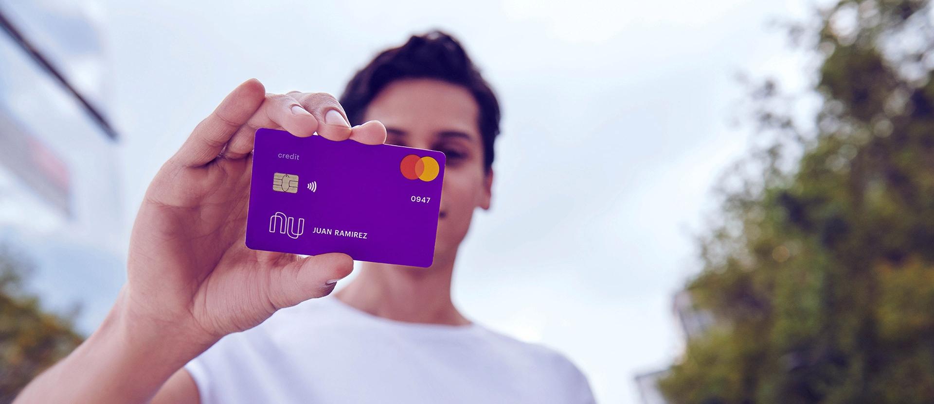 Un joven sostiene una tarjeta de crédito morada Nu con la inscripción de un nombre: