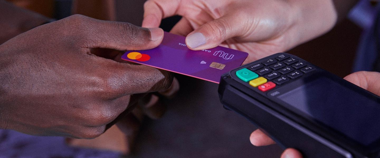 Se ve una mano entregando una tarjeta de crédito a otra mano que la posa sobre una terminal de pago