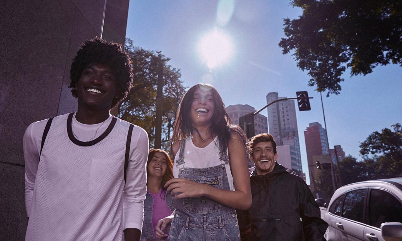 Cuatro jóvenes, dos mujeres y dos hombres, caminan y sonríen divertidos en una ciudad soleada.