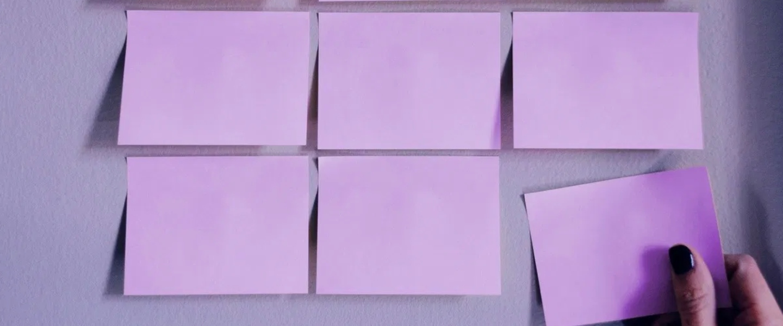 Una mano pega una nota adhesiva morada clarita en una pared de color similar.