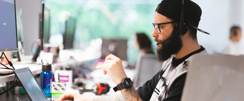 Un Nubanker -gorrita dada vuelta, anteojos de marco, brazos tatuados- lleva puestos auriculares y trabaja concentrado frente a su laptop