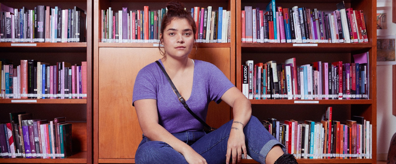 Una mujer joven, con una camiseta morada, sentada en el piso, delante de una biblioteca, mira hacia el frente con firmeza.