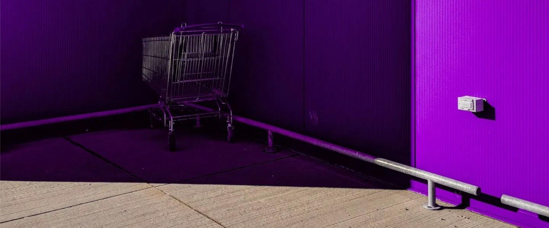 Un carrito de supermercado en un rincón a la sombra de color morada y una franja de sol por delante.