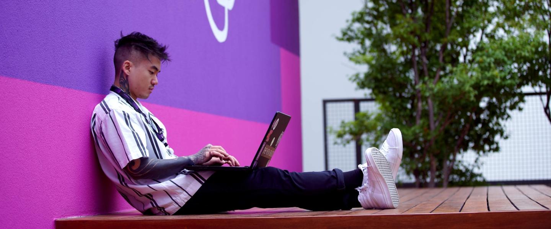 Un joven tatuado está sentado en el piso de un deck contra una pared morada que tiene la inscripción Nu, mientras usa su laptop.
