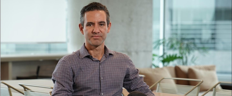 David Vélez posa sentado en una oficina con una camisa a cuadros y jeans negros.