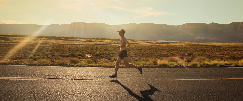 Un hombre corre solo, con el torso desnudo, en medio de una ruta que pasa cerca de una montaña