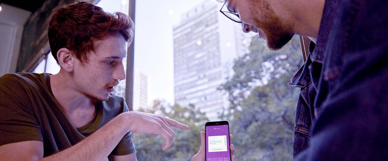 Un joven con un piercing en la nariz le muestra al otro un celular con la app morada de Nu Colombia en el inicio de la fase beta de la moradita.