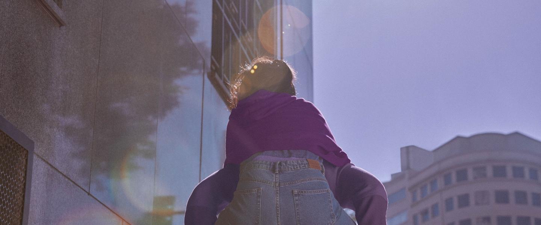 Una joven subida a caballo de otra persona se ve de espalda; usa jeans y un saco morado.