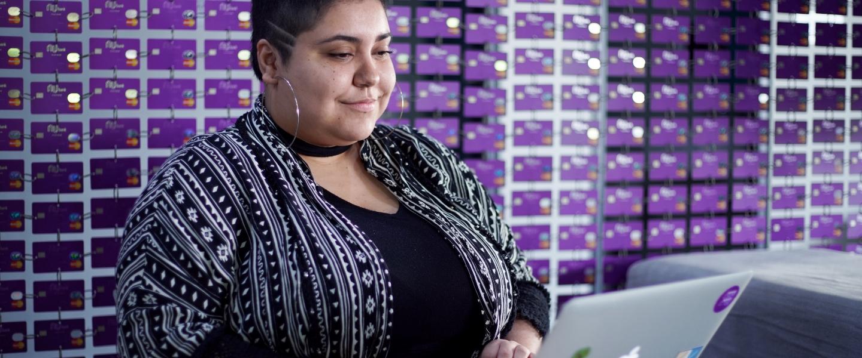 Una mujer con el cabello cortado al rape trabaja sobre su laptop apoyada en su regazo delante de un panel hecho con tarjetas de crédito Nu