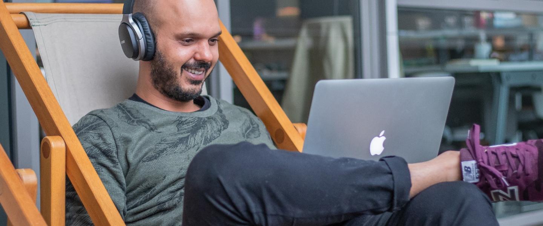 Un hombre joven, sonriente, barbado, está sentado en una reposera de madera y lona trabajando en su Mac, usando auriculares.