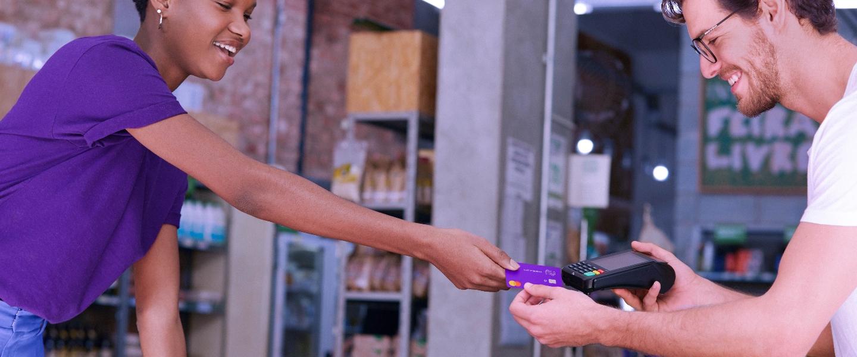 Una mujer joven con una camiseta morada le extiende su tarjeta de crédito Nu a un joven que sostienen un datáfono.