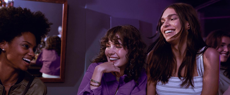 Tres mujeres ríen en un bar con paredes moradas y un gran espejo: Nubank supera los 35 millones de clientes en menos de siete años.