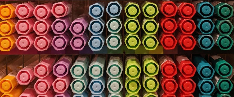 Varias tapas de marcadores de diferentes colores se ven alineados en un estante.
