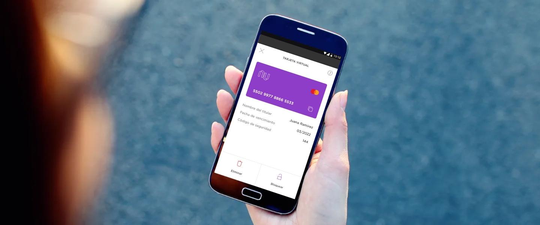 Una mano sostiene un celular en cuya pantalla se ve la tarjeta virtual Nu, en la app de Nu.