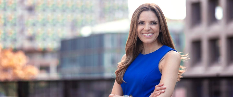 Cata Bretón, gerente general de Nu, sonríe adelante de altos edificios: ha sido seleccionada como una de las 50 mujeres poderosas