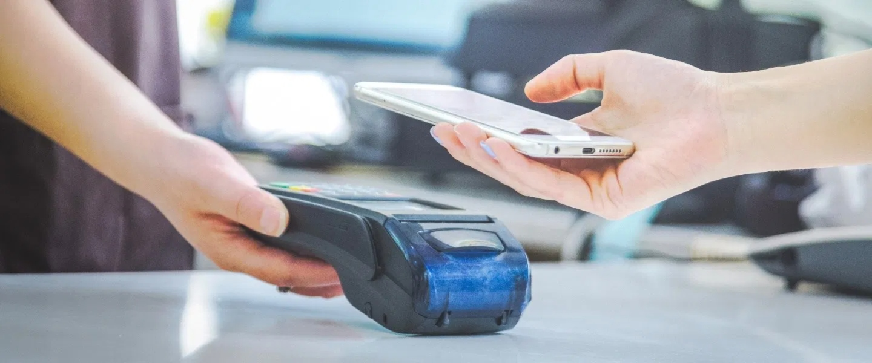 Educación financiera Nu. Se ve una mano acercando un teléfono celular a un datáfono.
