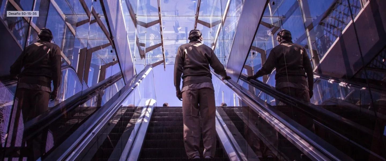 Un hombre joven sube de espaldas en una escalera mecánica: se dirige al próximo nivel de cómo ahorrar dinero con la regla 50-15-35