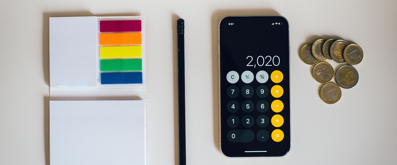 Una calculadora, un lápiz y unos postit de colores para entener los tipos de presupuesto que mejor se ajustan a tu vida financiera.