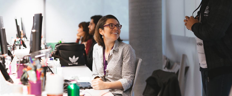 Programadores de Nu Colombia. Una ingeniera de software, sentada en su escritorio, conversa con un compañero.