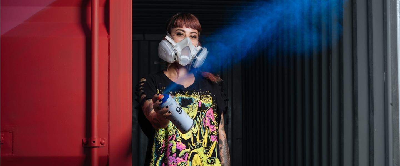 La neomuralista colombiana Ledania con una máscara y accionando un aerosol. Es quien diseñó el dibujo del Kit de Bienvenida de Nu.