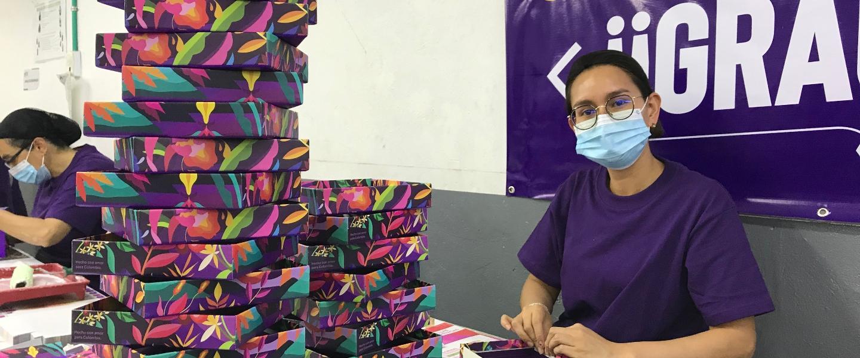 Una trabajadora de dígitos&diseños posa mientras arma el Kit de Bienvenida de la tarjeta de crédito Nu.