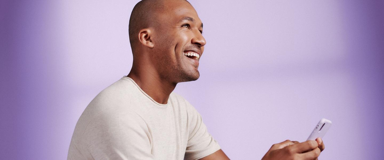 Un hombre sonríe mirando al cielo mientras sostiene un celular en su mano: llamó al teléfono NU
